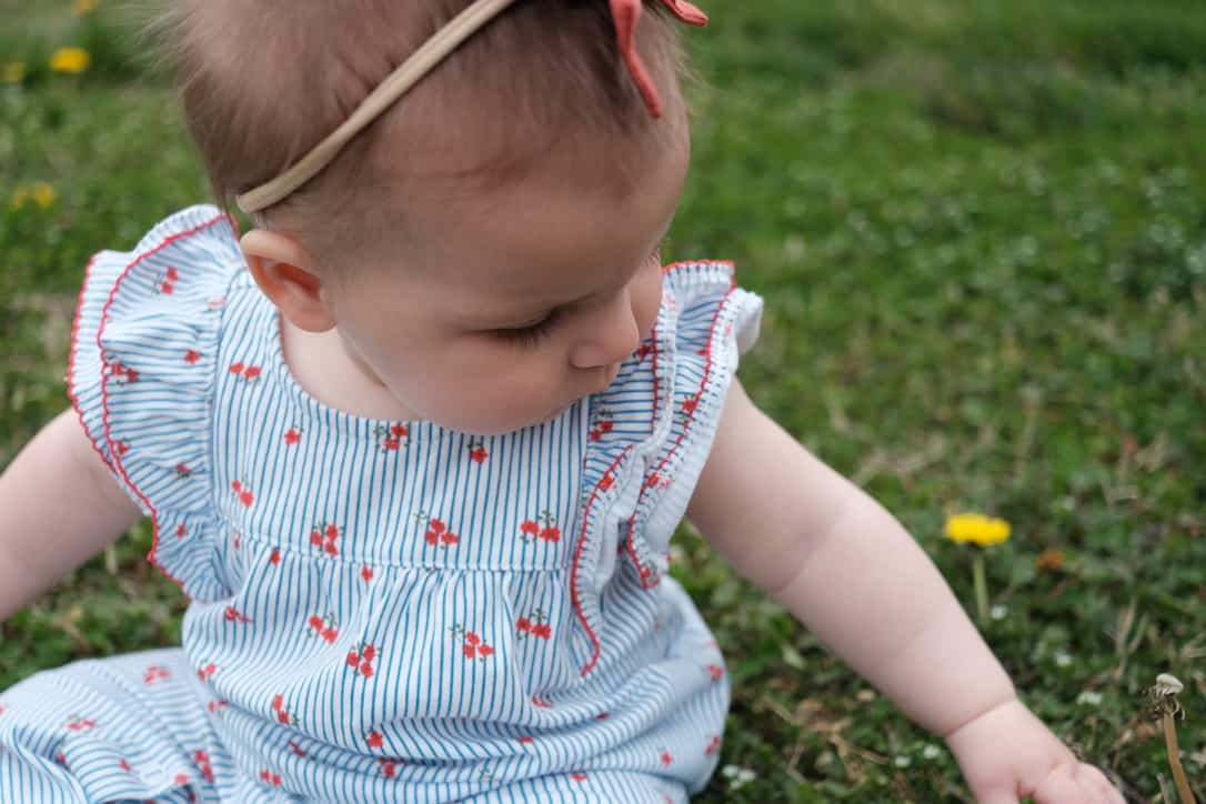 baby playing in grass