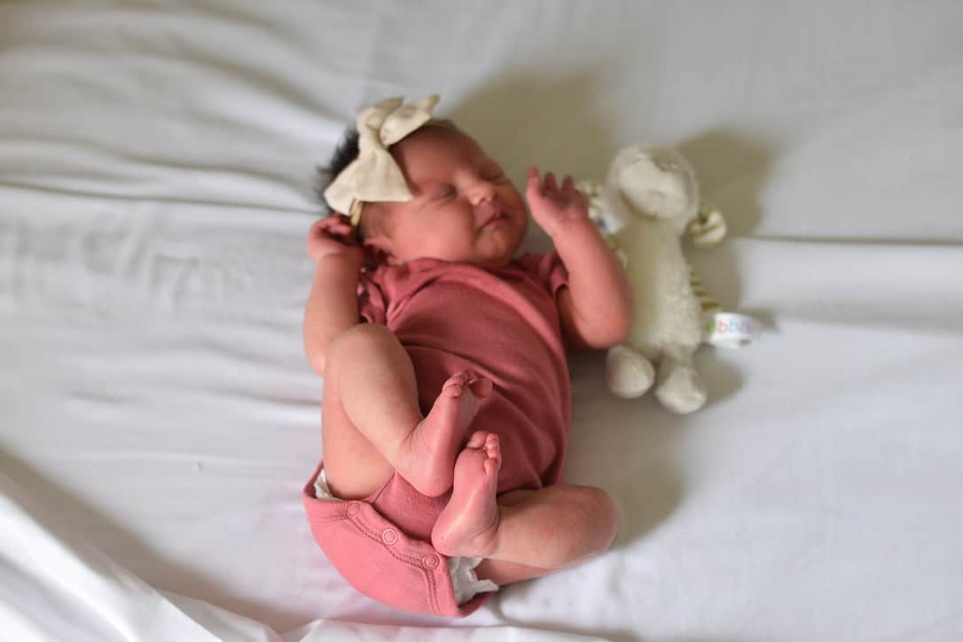 newborn laying on bed with pink short sleeve onesie
